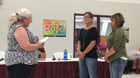Sally Pflaumer, business manager, administers the oath of office to new board members Lisa Wendt and LeeAnn Gaer